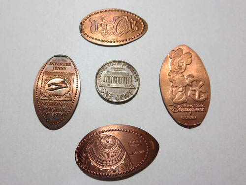 Pressed pennies, compared to a US penny coin. Only the top and left ones are made from actual pennies.